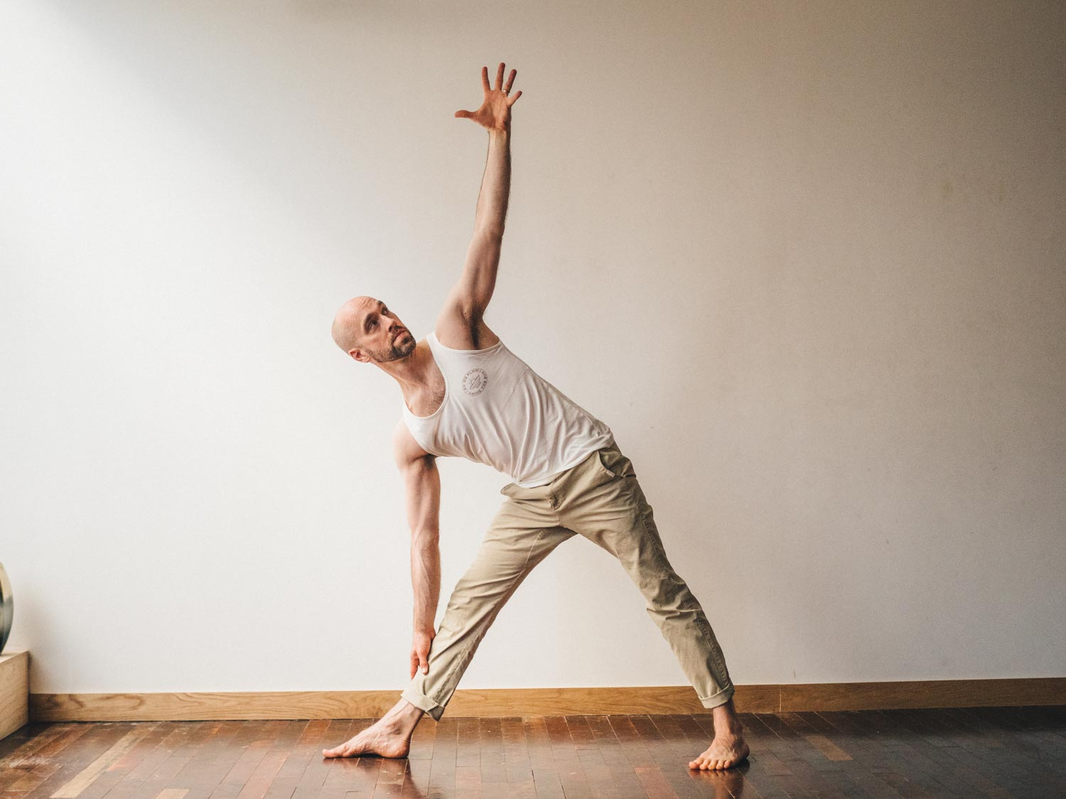 Man doing Uttihita Trikonasana or extended triangle pose yoga pose