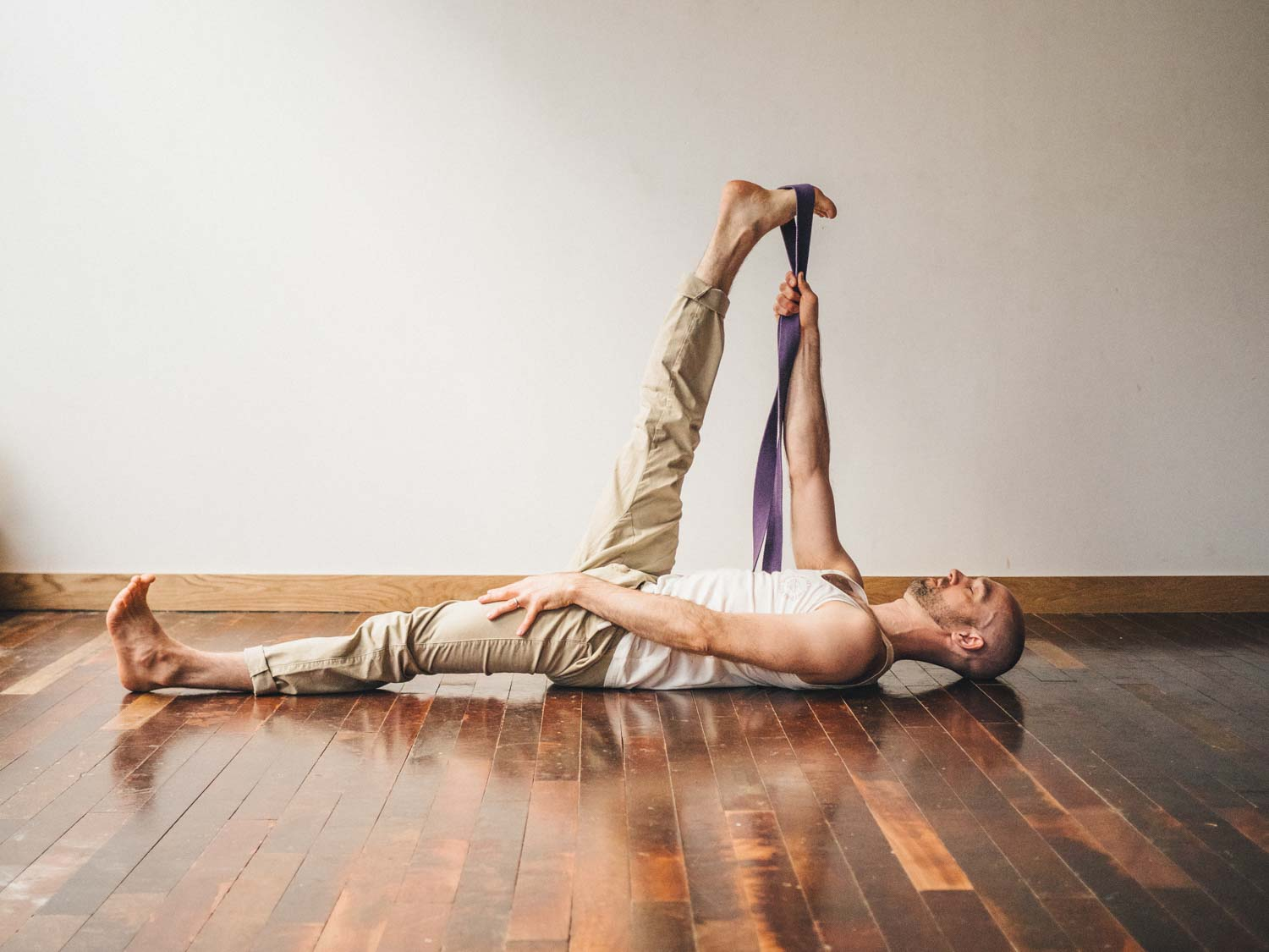 Man doing a strap assisted hamstring stretch