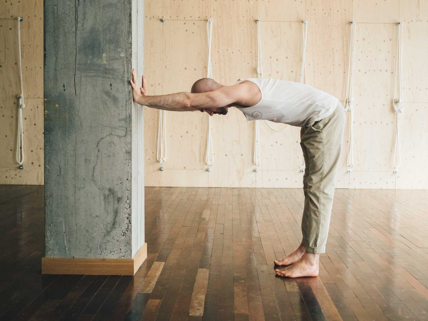 Man doing a shoulder stretch against a wall