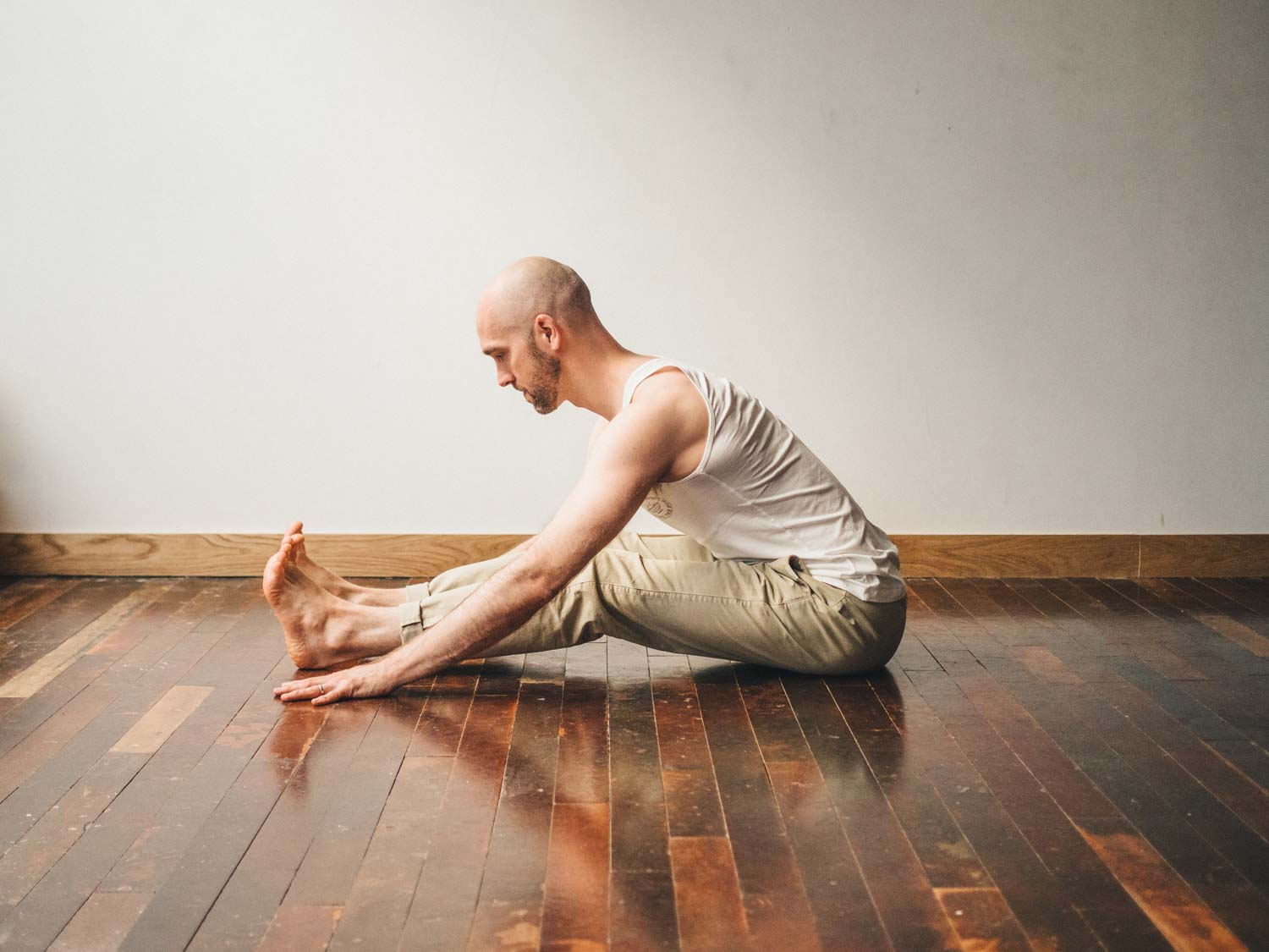 Man doing Paschimottanasana or seated forward fold yoga pose