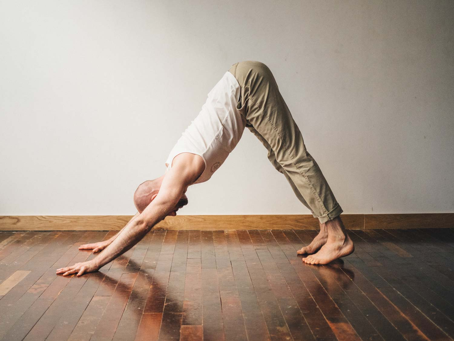 Man doing Adho Mukha Svanasana or downward dog yoga pose