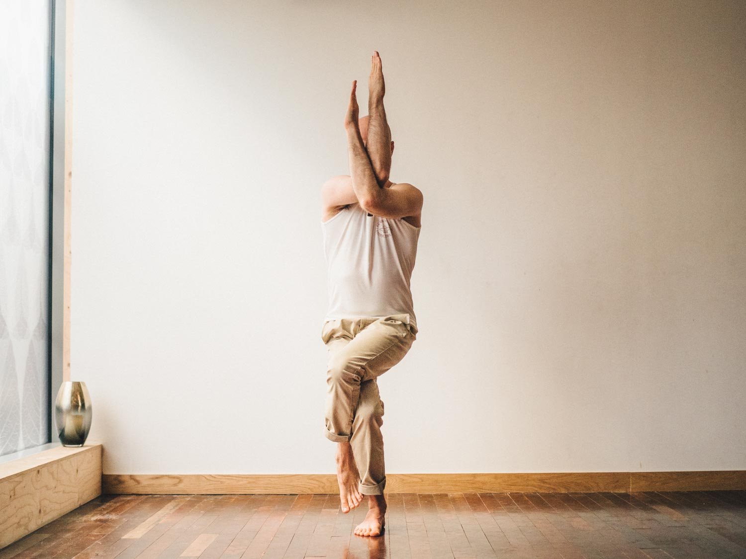 Man doing eagle pose or Garudasana in yoga studio