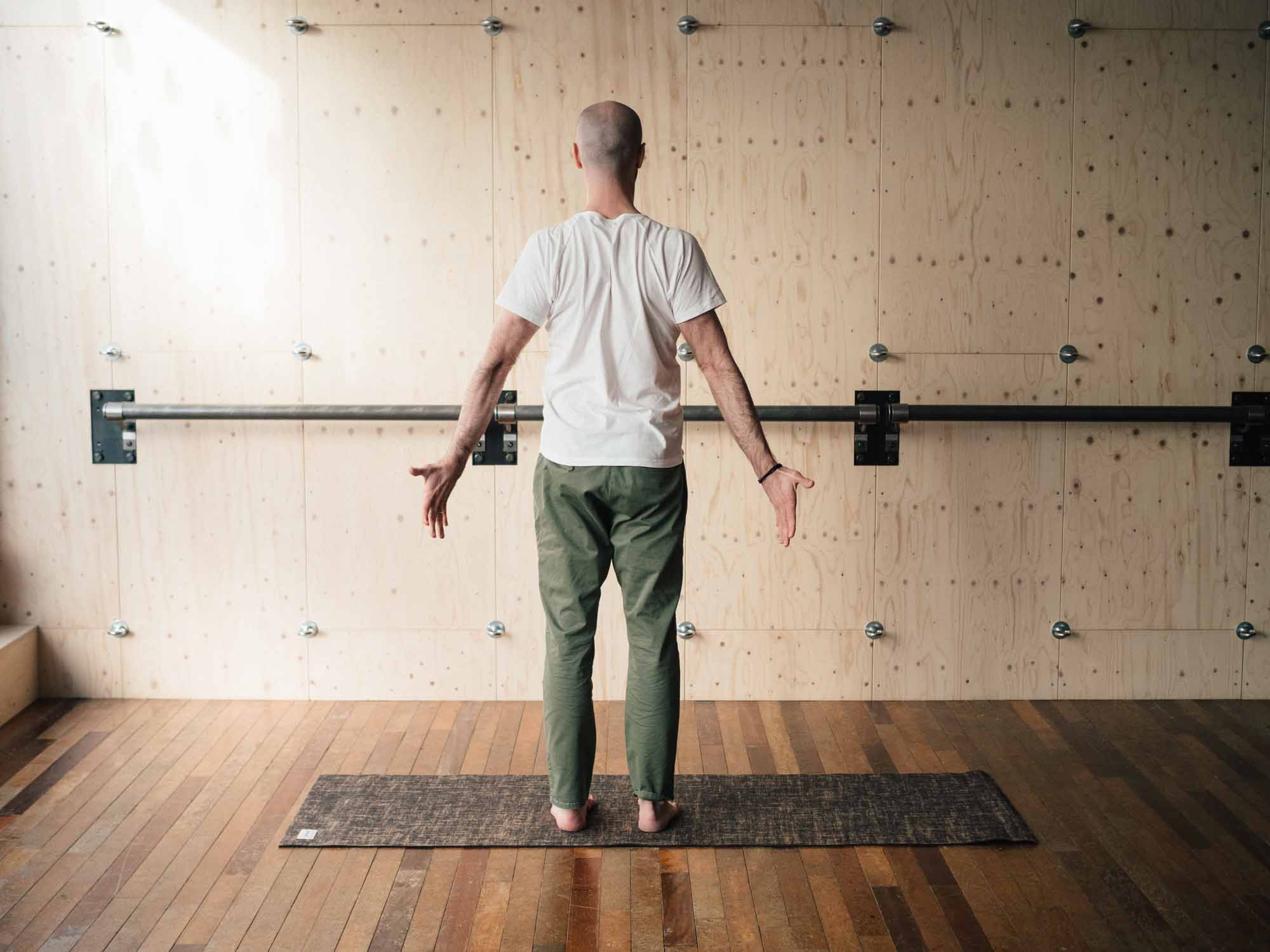 Man squeezing shoulder blades together in a yoga studio