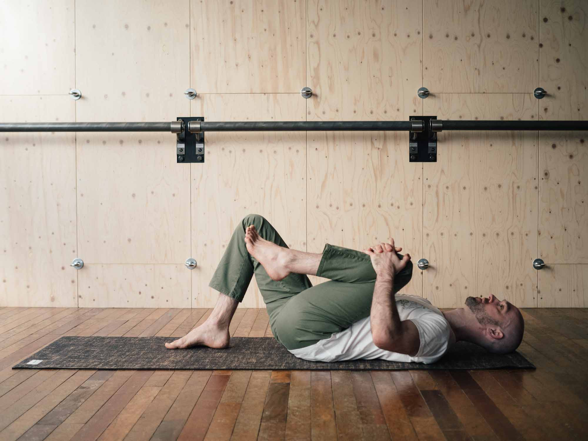 Man pulling one knee to his chest in a yoga studio