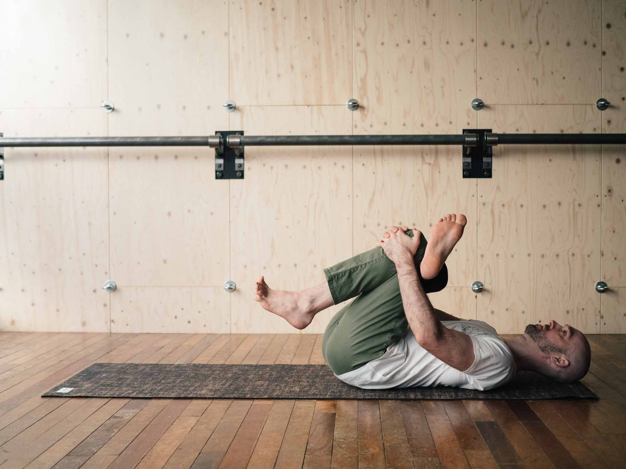Man doing threading the needle pose in a yoga studio