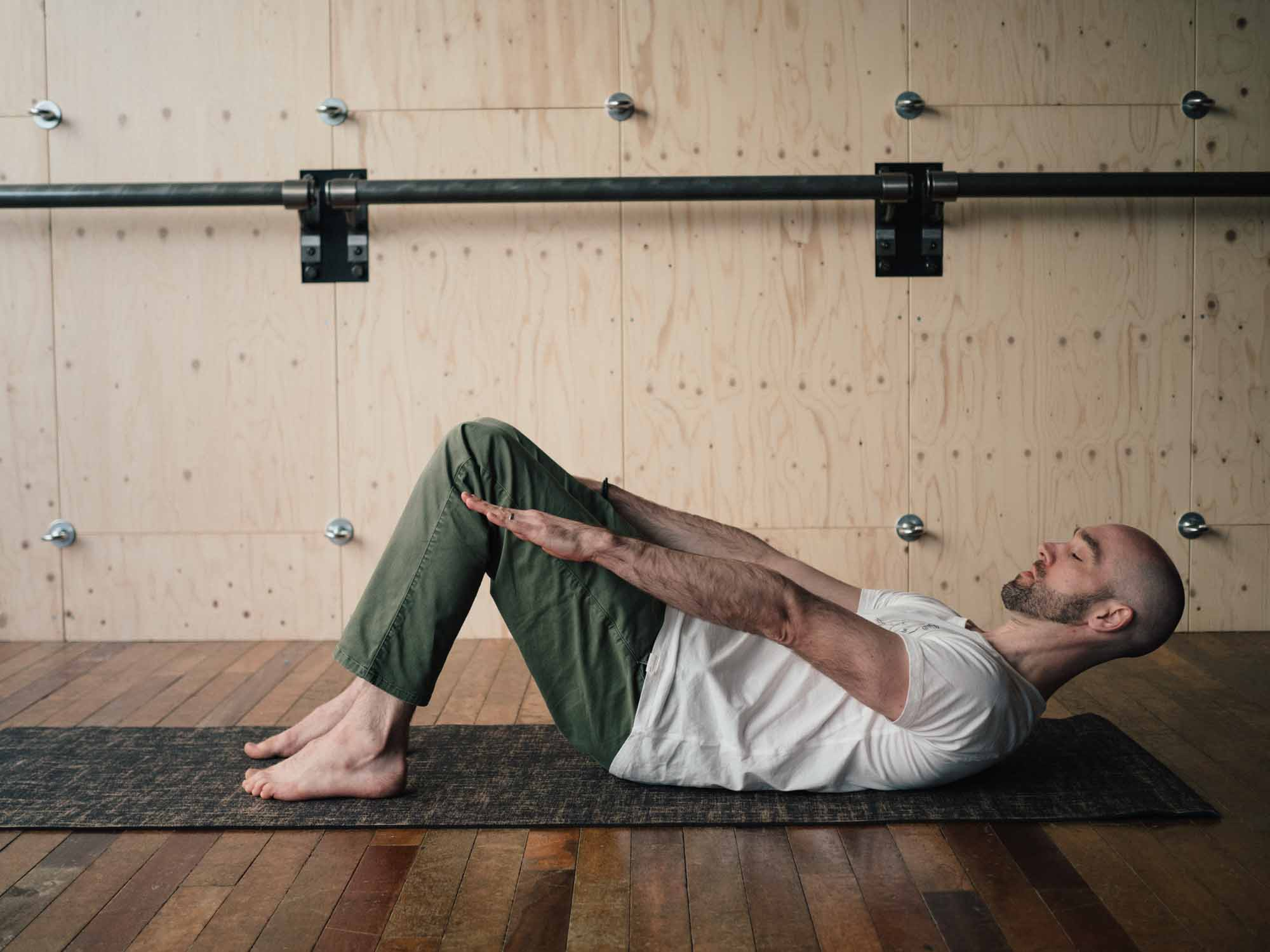 Man doing abdominal crunches in a yoga studio