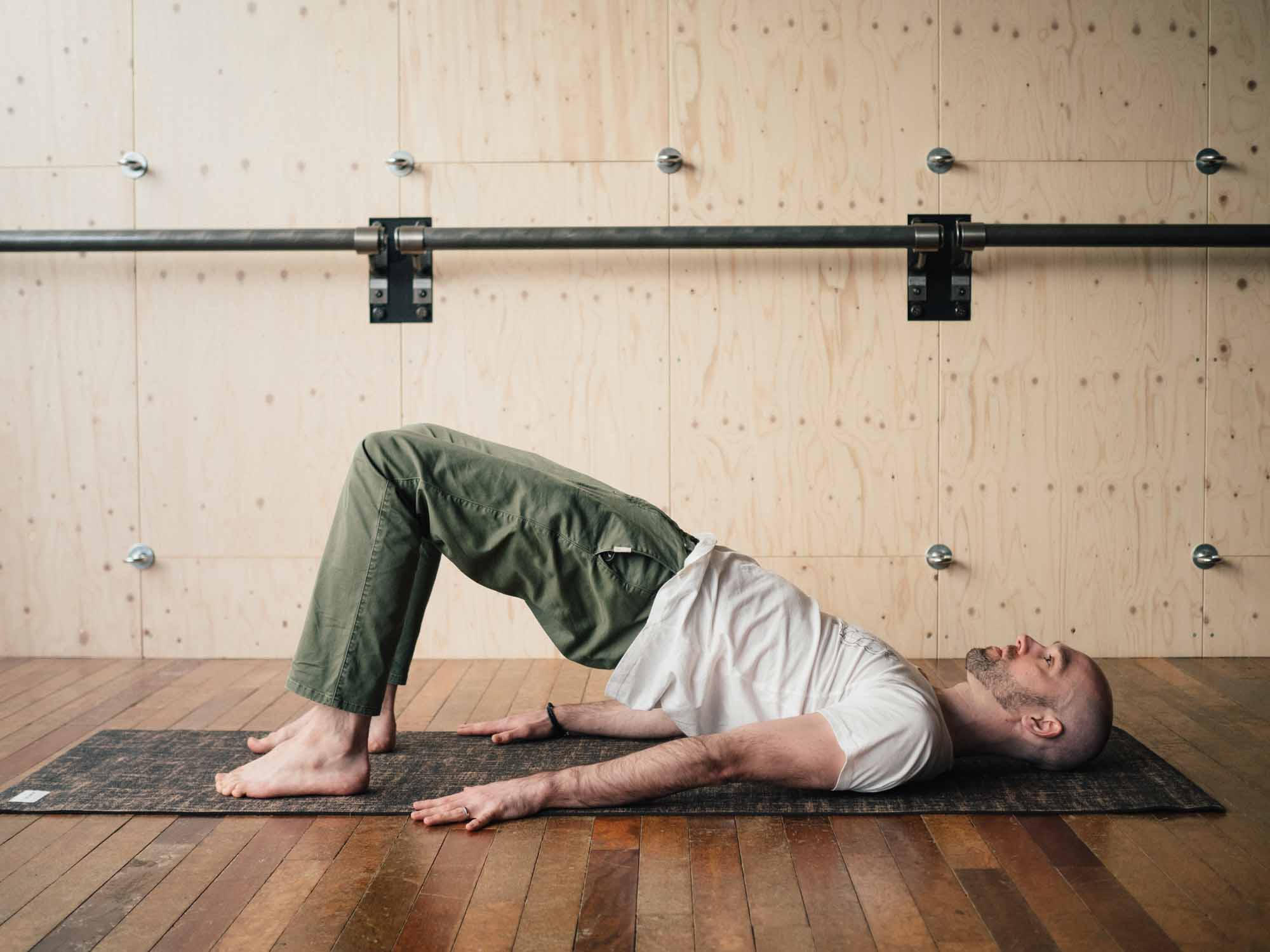 Man doing bridge pose in a yoga studio