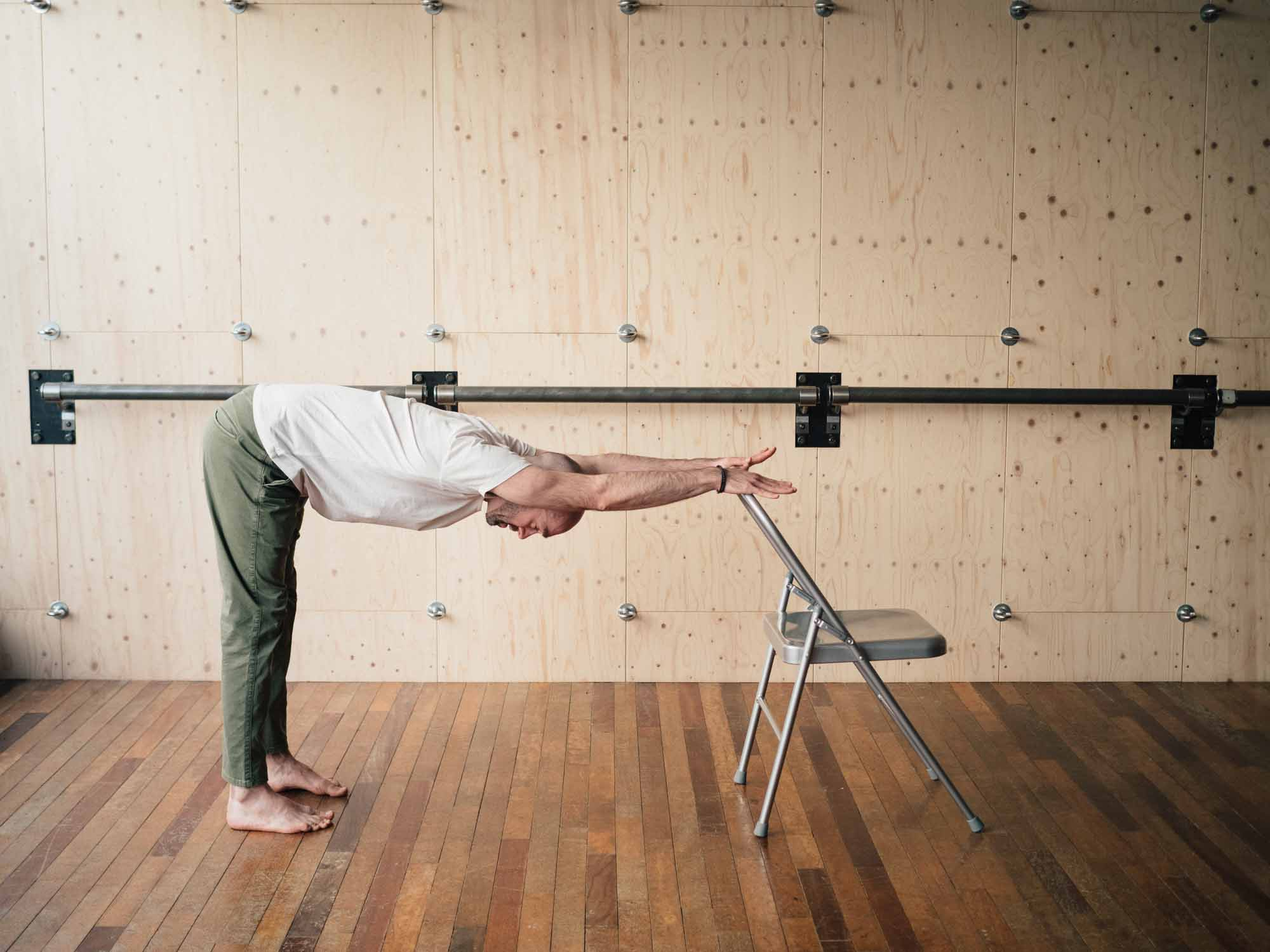 Man doing modified downward dog yoga pose on an office chair in a yoga studio