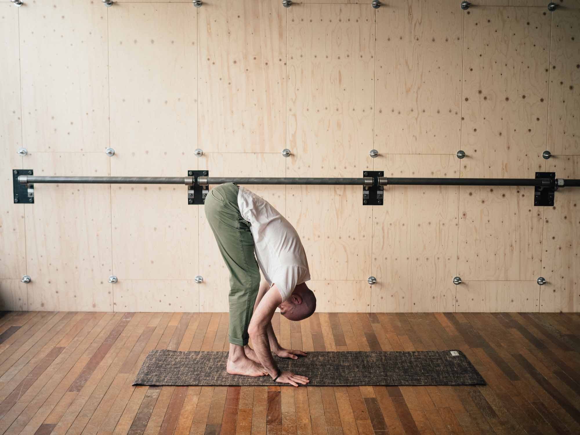 Man doing uttanasana yoga pose in a yoga studio
