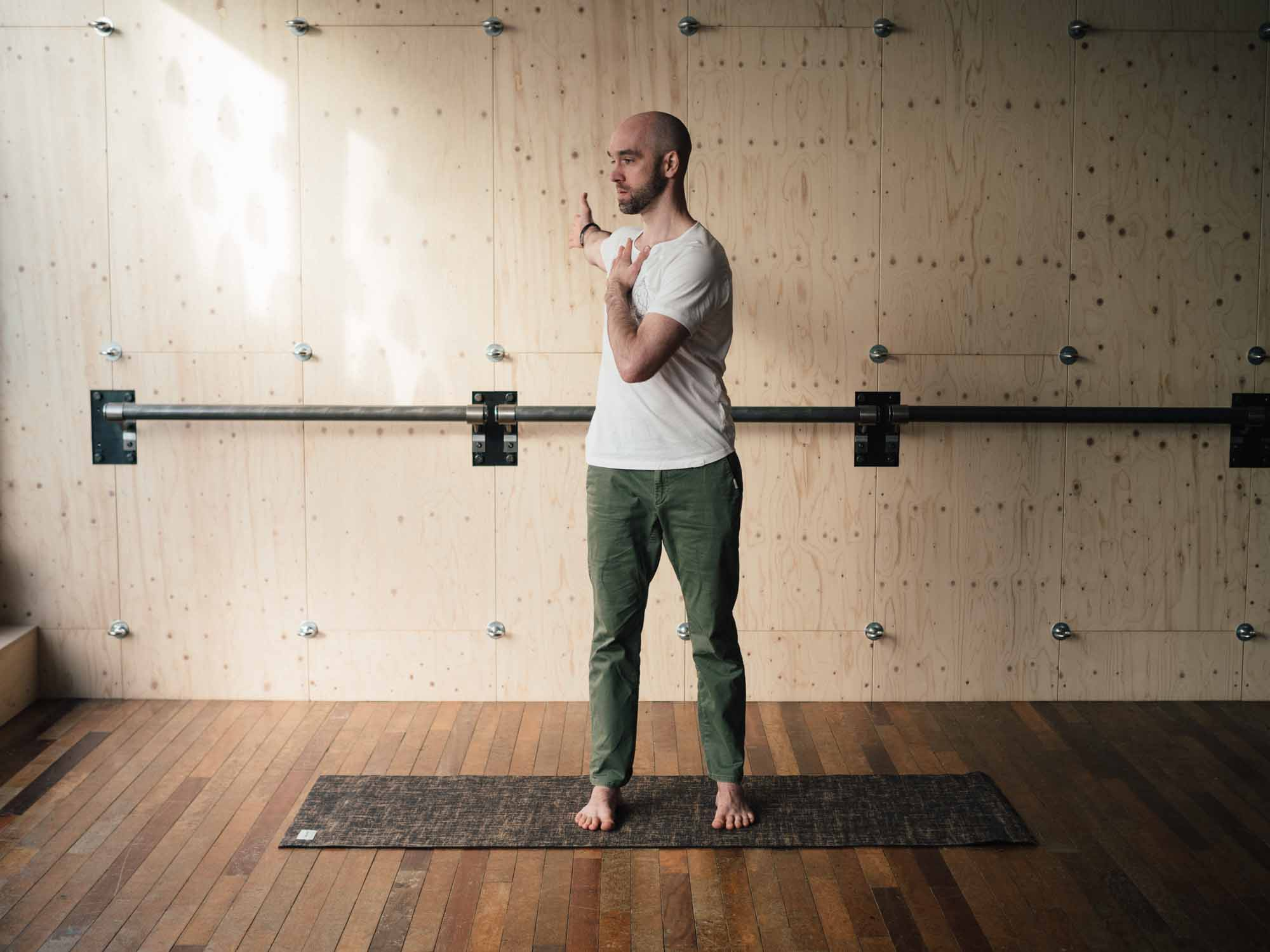 Man doing a standing twist in a yoga studio