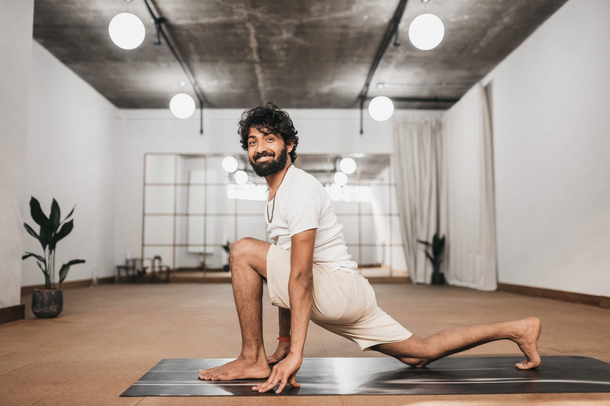 Ravi Dixit doing a lunge in a yoga studio