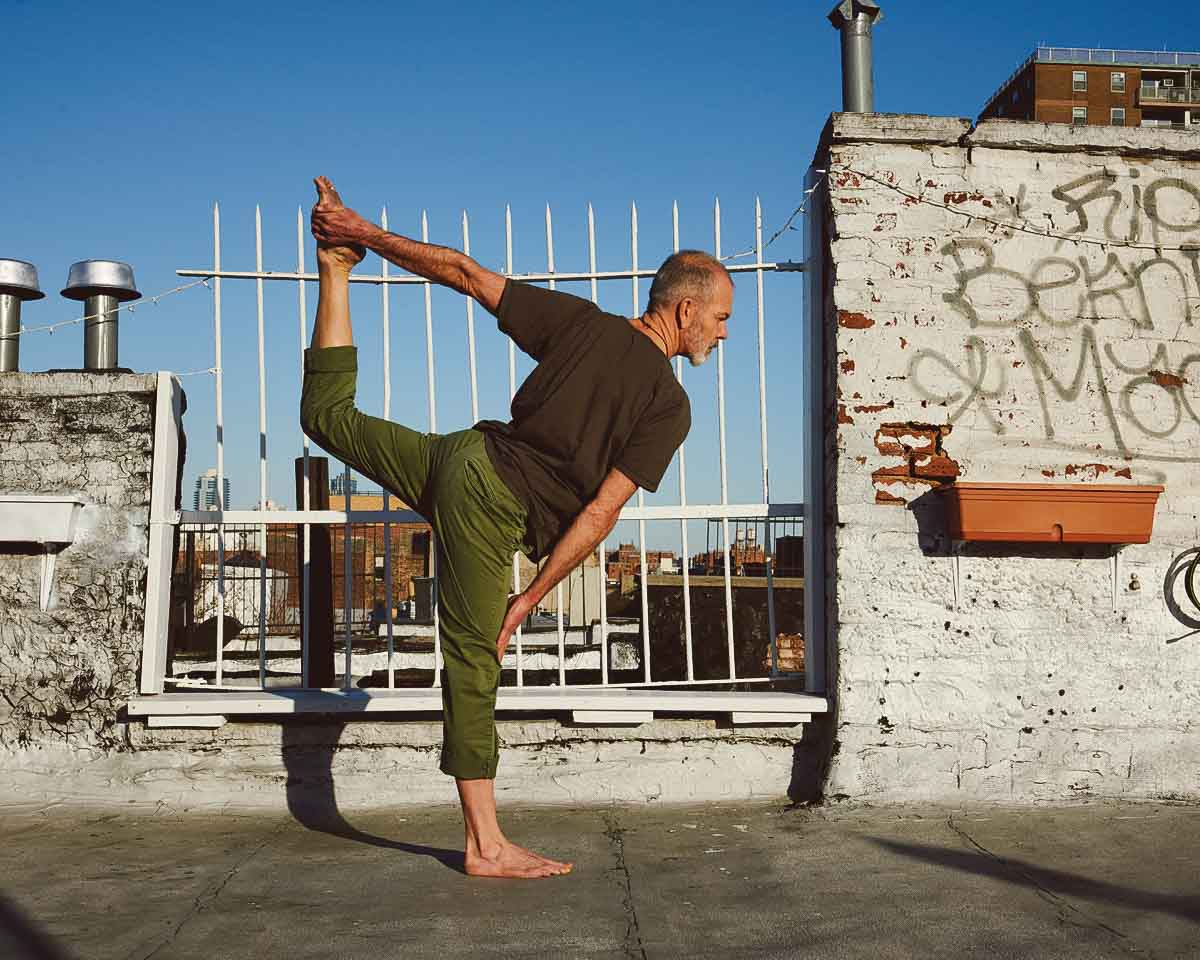 Man doing yoga on a rooftop