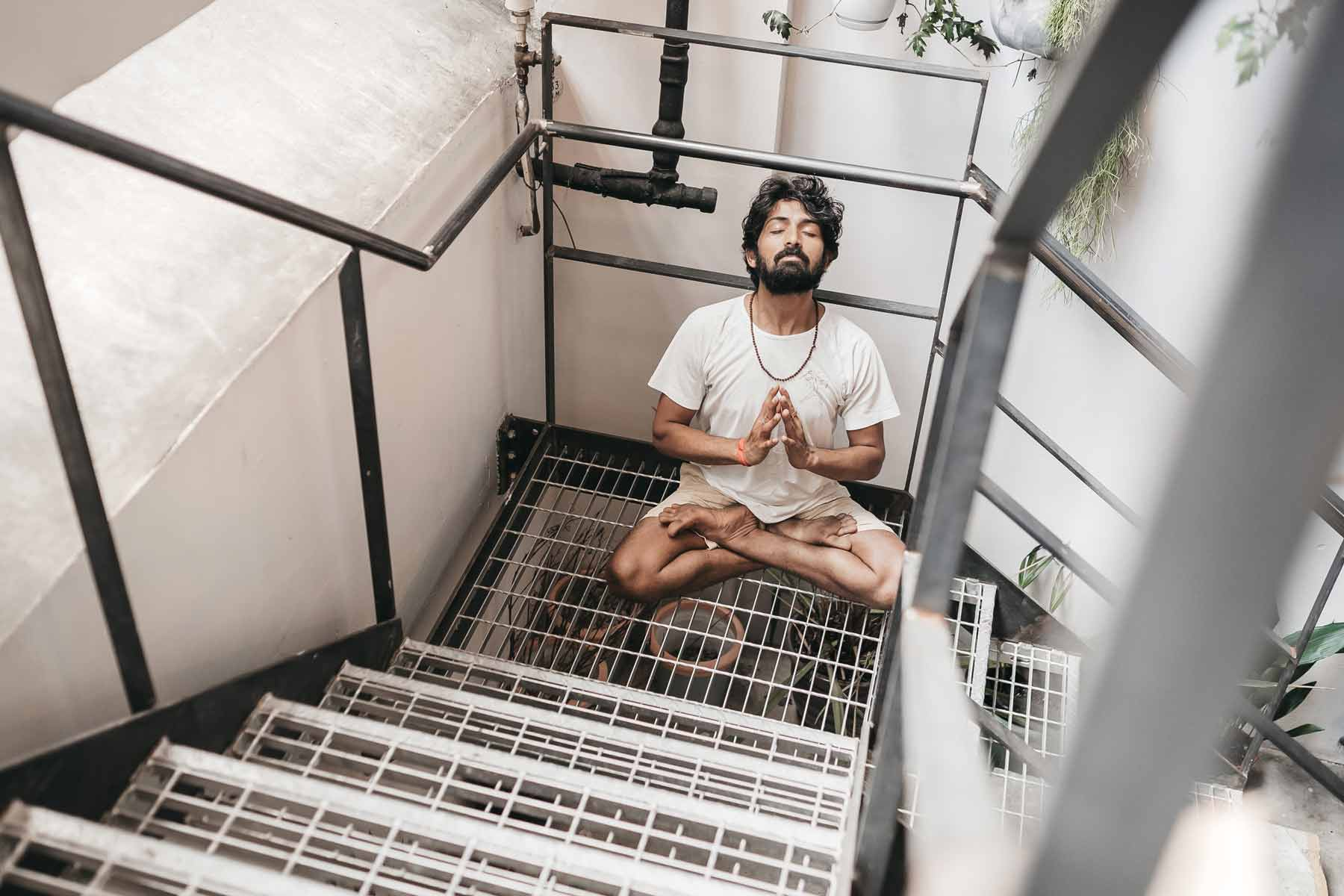 Man meditating on staircase wearing So We Flow...