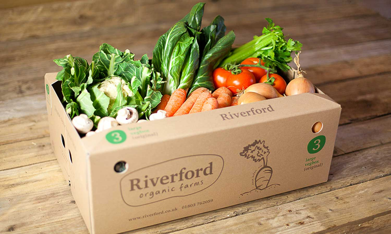 Riverford organic vegetable box on a wooden floor