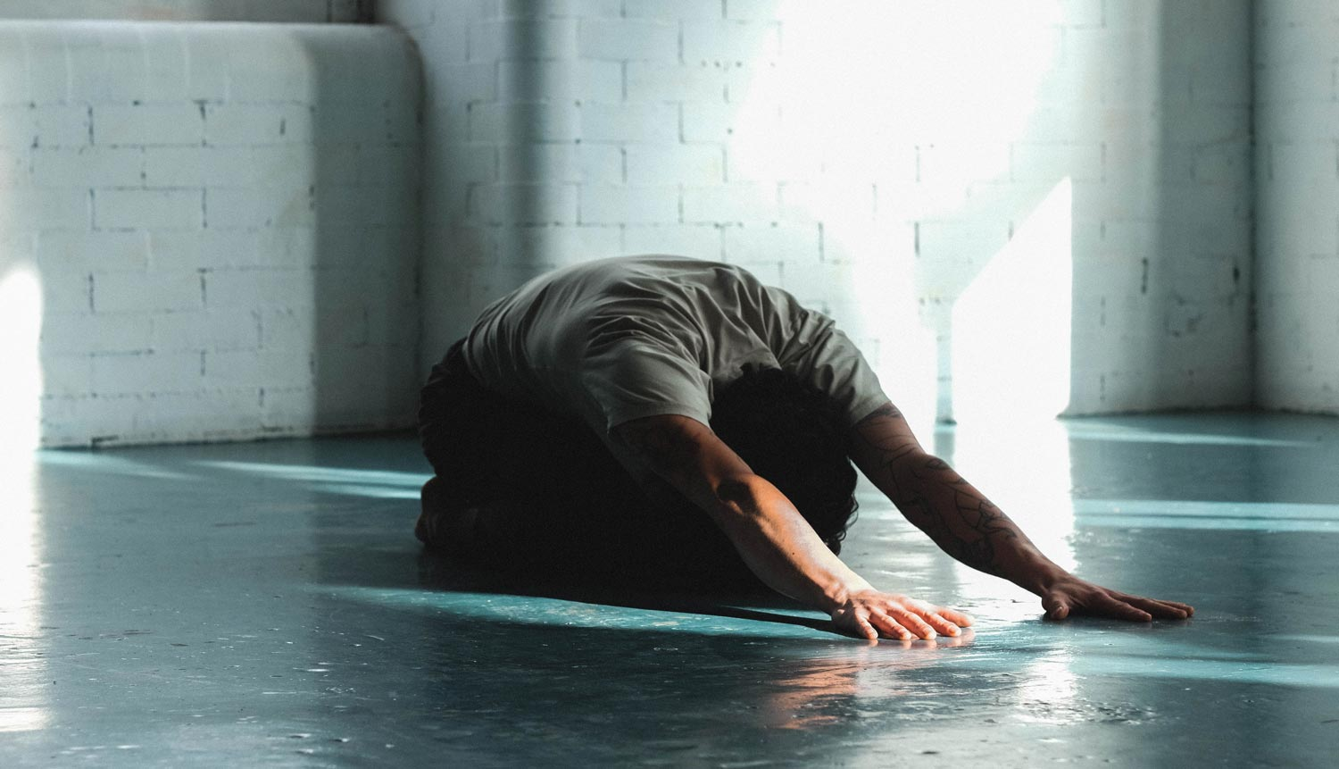 Man doing yoga in a warehouse