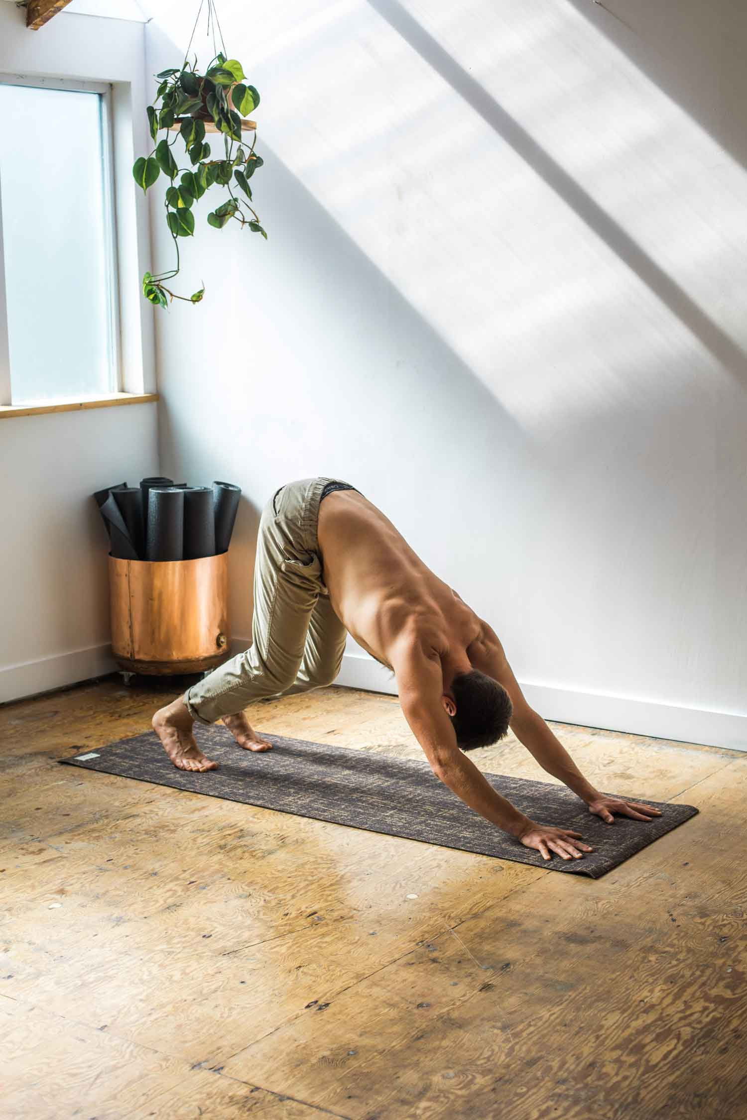 Man doing downward dog in a yoga studio