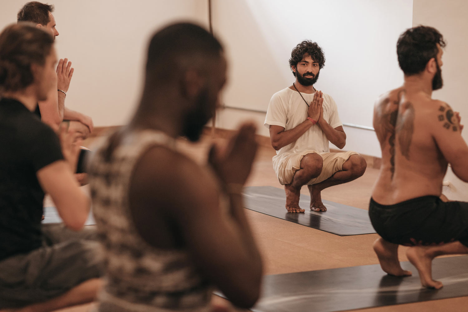 Male yoga teacher teaching a group of men