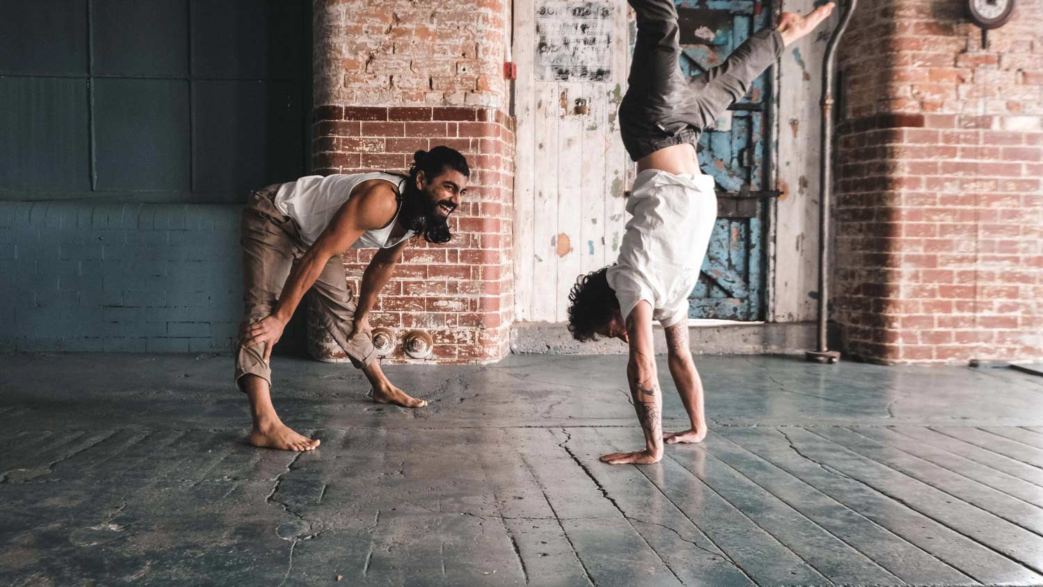 Man doing handstand with a laughing man watching