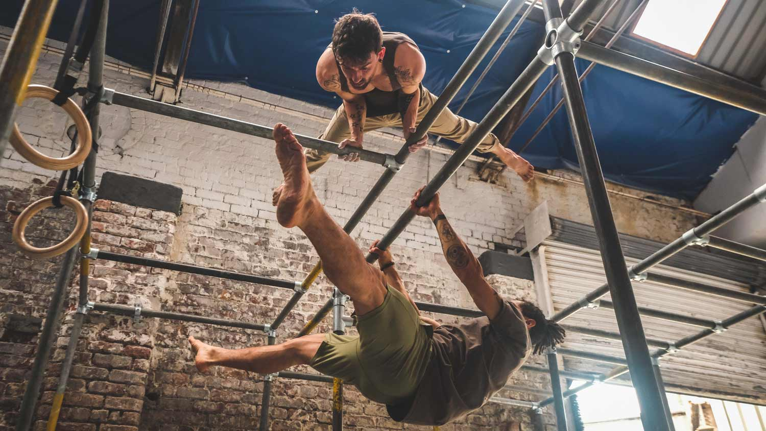 Two men doing calisthenics on scaffolding