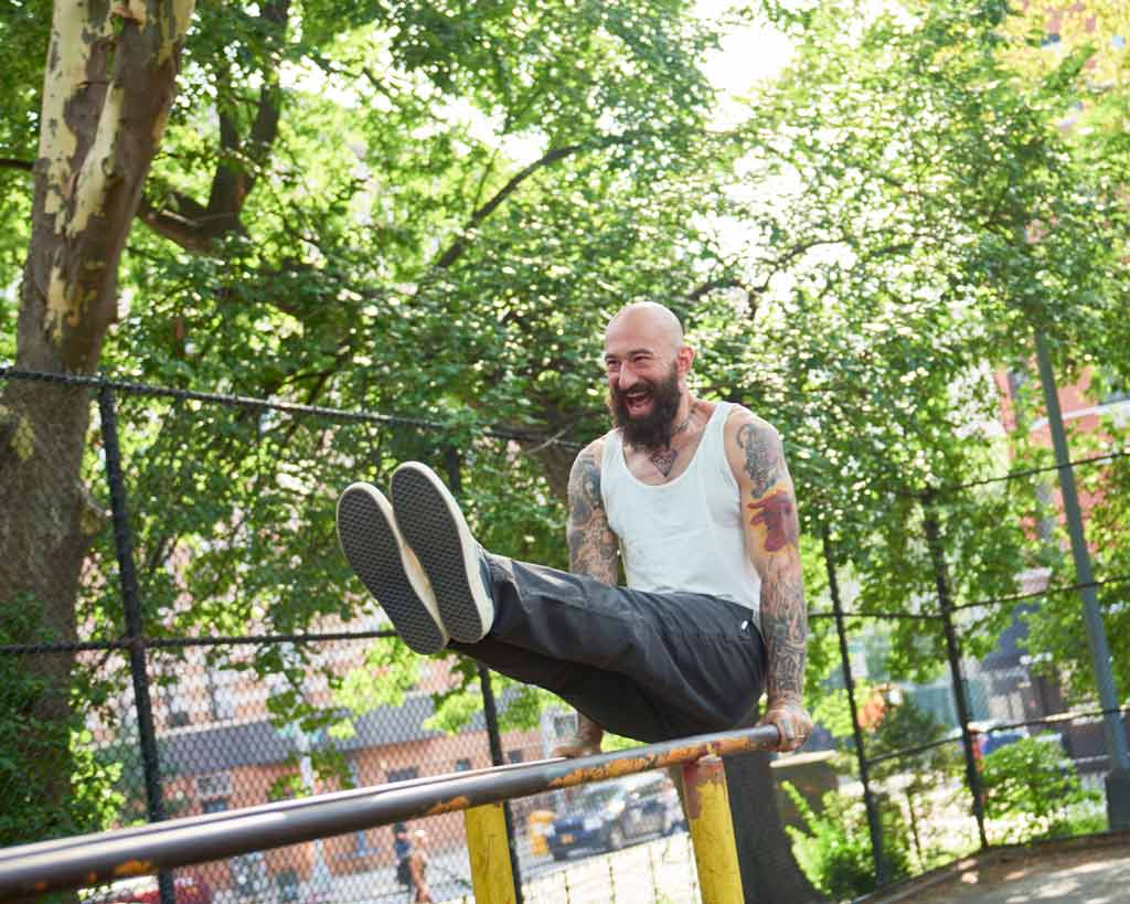 so we flow... Al Kavadlo doing an l-sit in a playground. Wearing natural jersey vest and beluga twill longs.