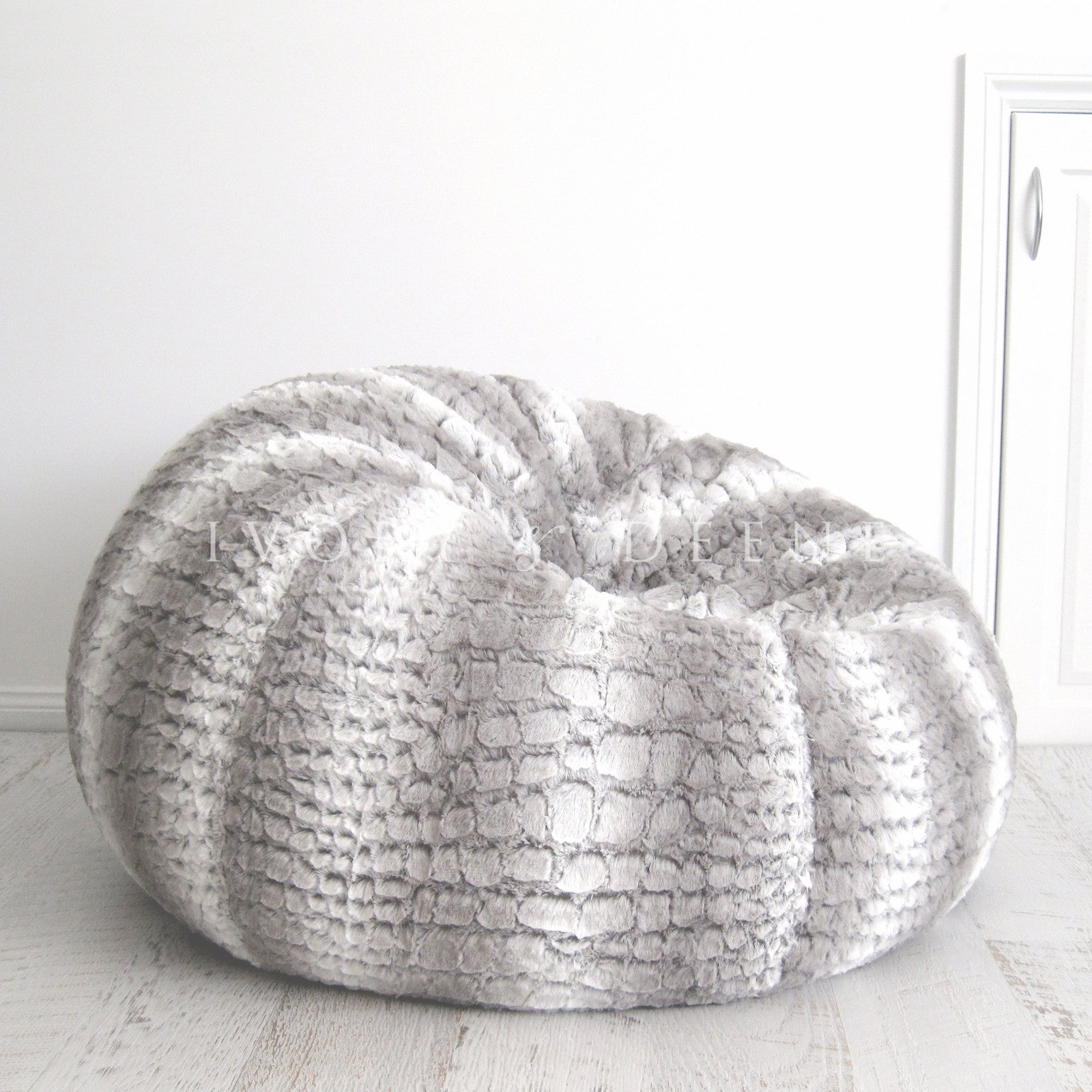 Faux Fur Bean Bag On A Wooden Floor Against White Wall
