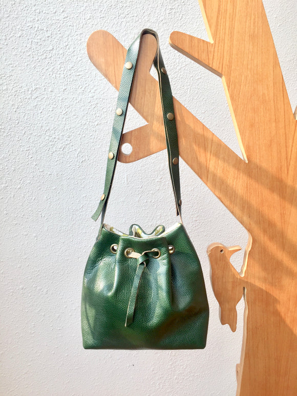 Green leather bucket bag with floral lining