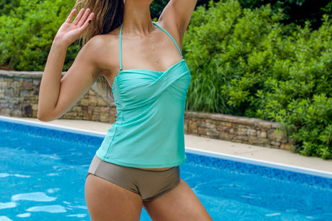 Woman by pool wearing seafoam blue tankini and bronze mid rise bikini bottoms