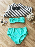 Flat lay of seafoam blue bandeau bikini top and seafoam blue high waisted bikini bottoms with black and white striped turkish towel and sunglasses