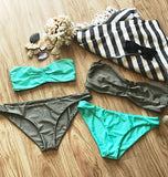 Flat lay of mix and match seafoam blue and bronze bandeau bikini top paired with bronze and seafoam blue cheeky bikini bottoms alongside black and white striped turkish towel and sunglasses.