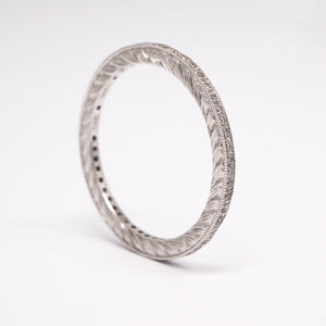 Hand-engraved 18K white gold diamond eternity wedding band with diamonds weighing a total of 0.13 carats and milgrain detail.