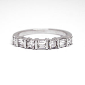 18K white gold diamond anniversary or wedding band with round diamonds weighing a total of 0.24 carats, and baguette diamonds weighing a total of 0.21 carats.