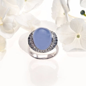 white gold cabochon-cut blue calcedony ring with pave set sapphires and diamonds