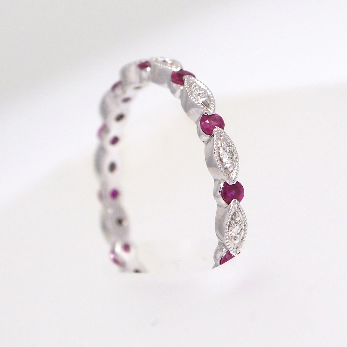 18K white gold eternity wedding band with 12 rubies weighing a total of 0.36 carats, and 12 diamonds weighing a total of 0.12 carats.