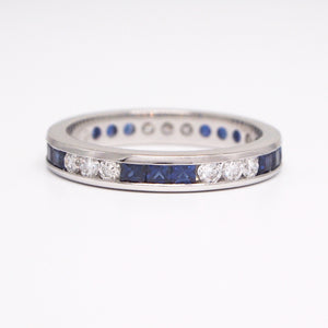 Platinum sapphire and diamond eternity ring with princess-cut sapphires weighing a total of 0.90 carats, and round diamonds weighing a total of 0.50 carats.