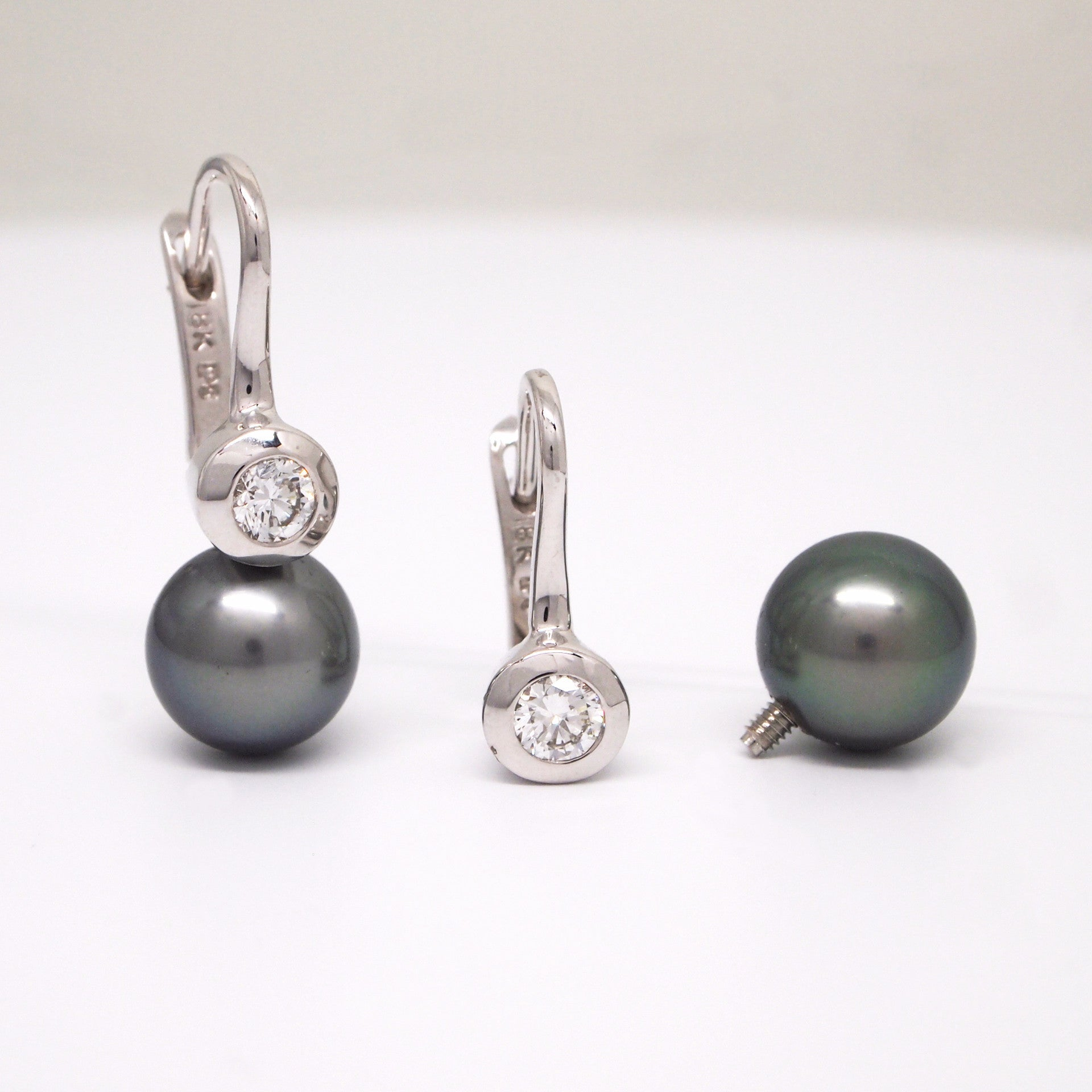 18K white gold diamond and Tahitian pearl earrings with 2 bezel-set diamonds weighing a total of 0.40 carats, and 2 removable (screw off) round 9.5mm black Tahitian pearls.