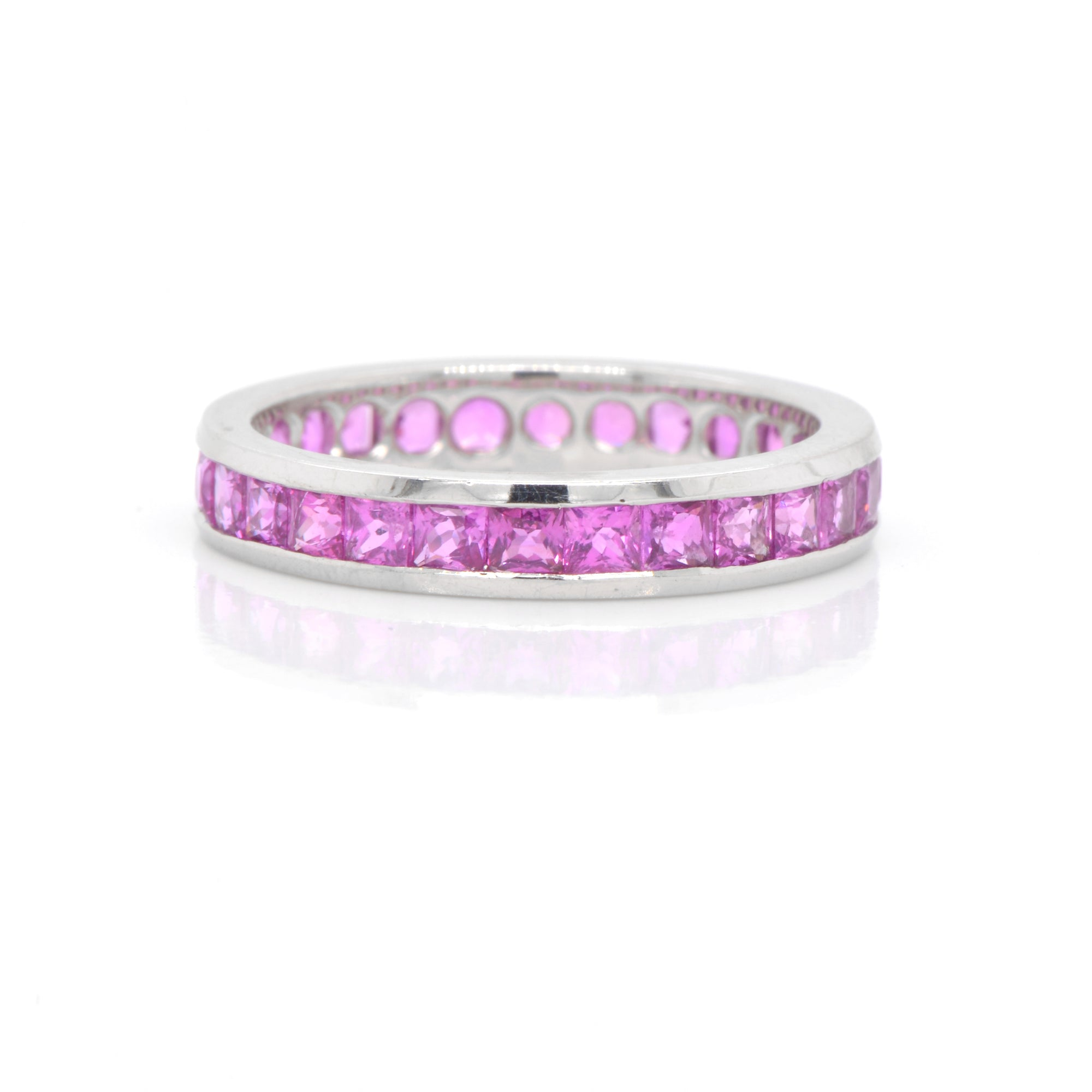 Platinum sapphire eternity band featuring princess-cut pink sapphires (2.43ctw) channel set in bright, white platinum in a full eternity design.