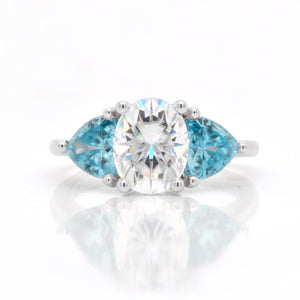 Judith Arnell Jewelers 14K white gold moissanite and zircon ring featuring one 2.00 carat oval moissanite, and 2 trillion-cut blue zircons weighing a total of 2.32 carats set in a 3-stone design.