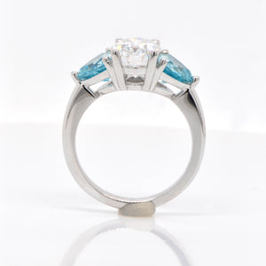 14K white gold moissanite and zircon ring featuring one 2.00 carat oval moissanite, and 2 trillion-cut blue zircons weighing a total of 2.32 carats set in a 3-stone design. Judith Arnell Jewelers