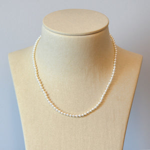 Pearl strand necklace featuring round freshwater pearls (4mm) and a 14K white gold marquis-shaped clasp.