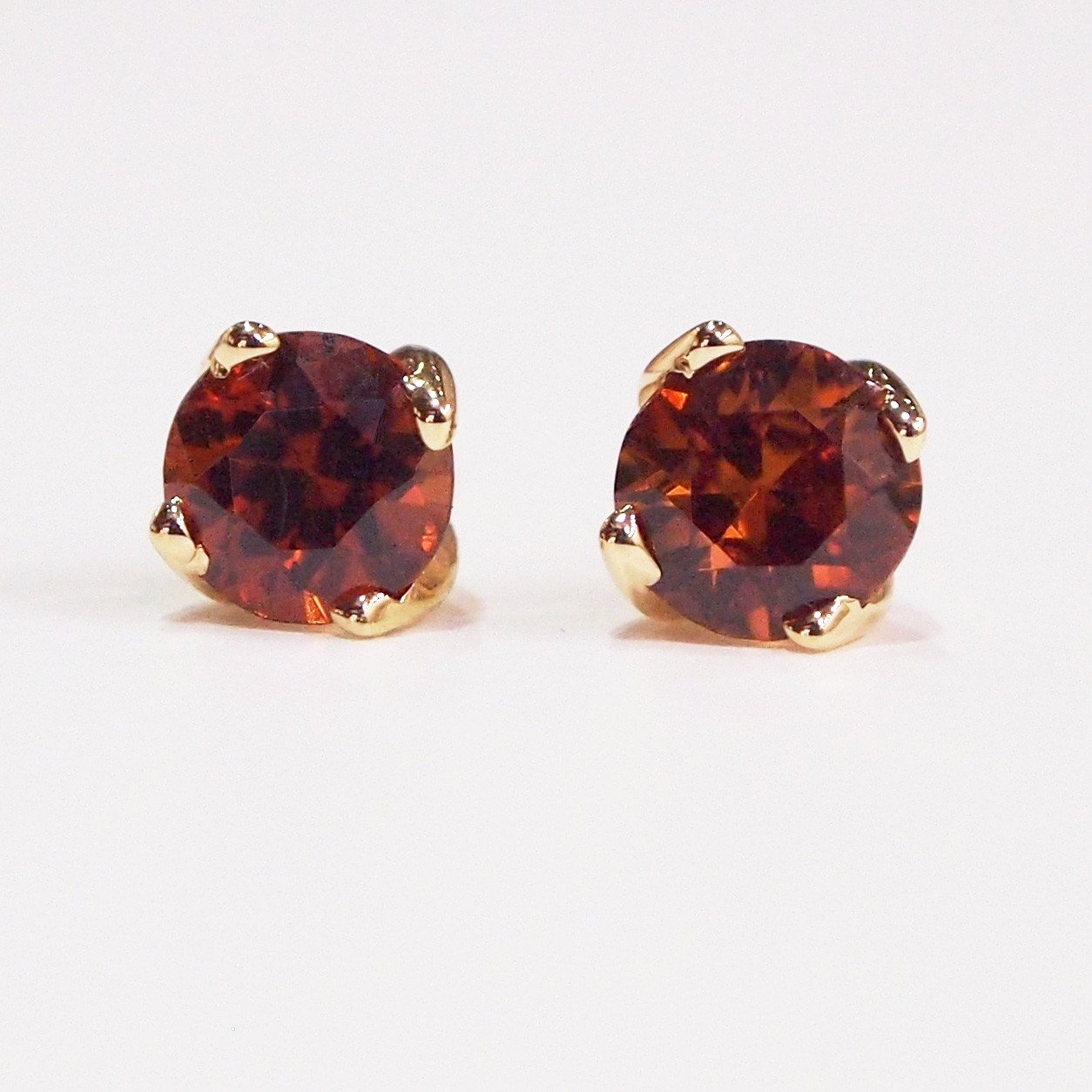 14K yellow gold 4-prong earring studs with two zircons weighing a total of 1.25 carats