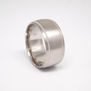 14K white gold 10mm man's wedding band featuring a low dome satin finish with thin milgrain edges.
