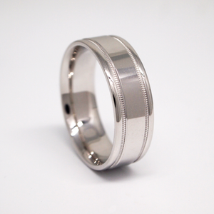 14k white gold 7MM man's wedding band featuring a bright finish with milgrain channels.