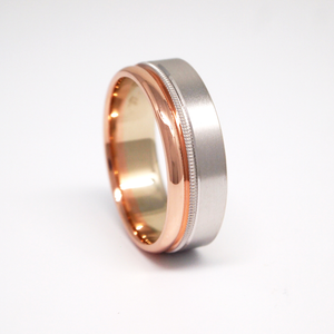 14K white and rose gold 7mm men's wedding band featuring a satin finish on white gold, offset milgrain channel, and high polish finish on rose gold.