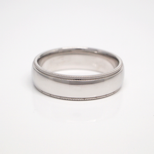 14K white gold 6mm domed men's wedding band featuring a high polish finish and milgrain edges.