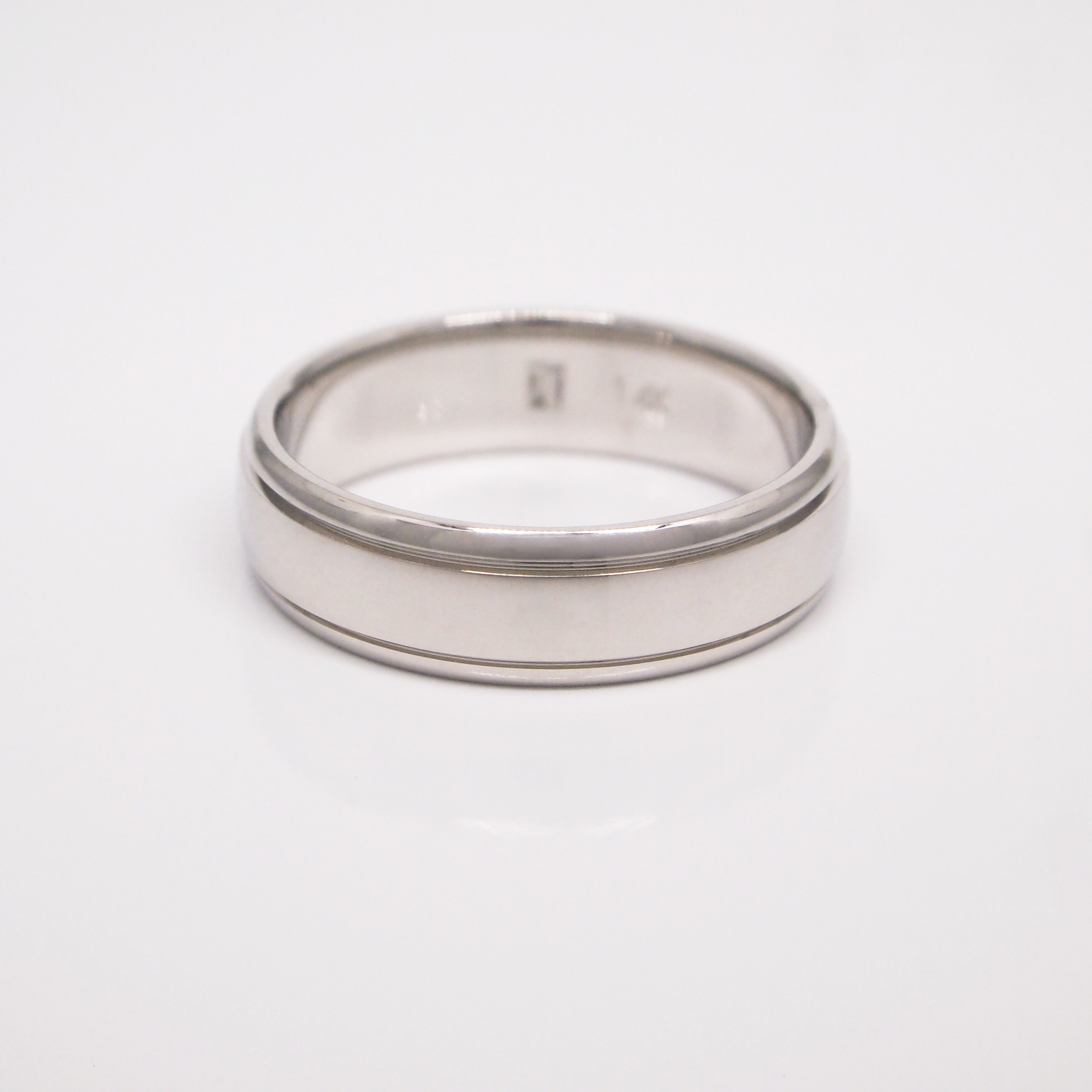 14K white gold 6mm men's wedding band featuring a medium dome, a high polish finish, and thin channels.