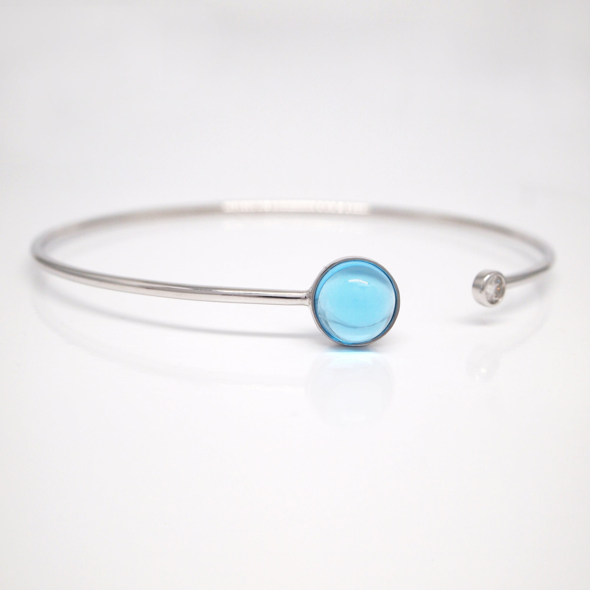 14K white gold bangle bracelet featuring an 8mm cabochon-cut blue topaz and a bezel-set brilliant-cut diamond