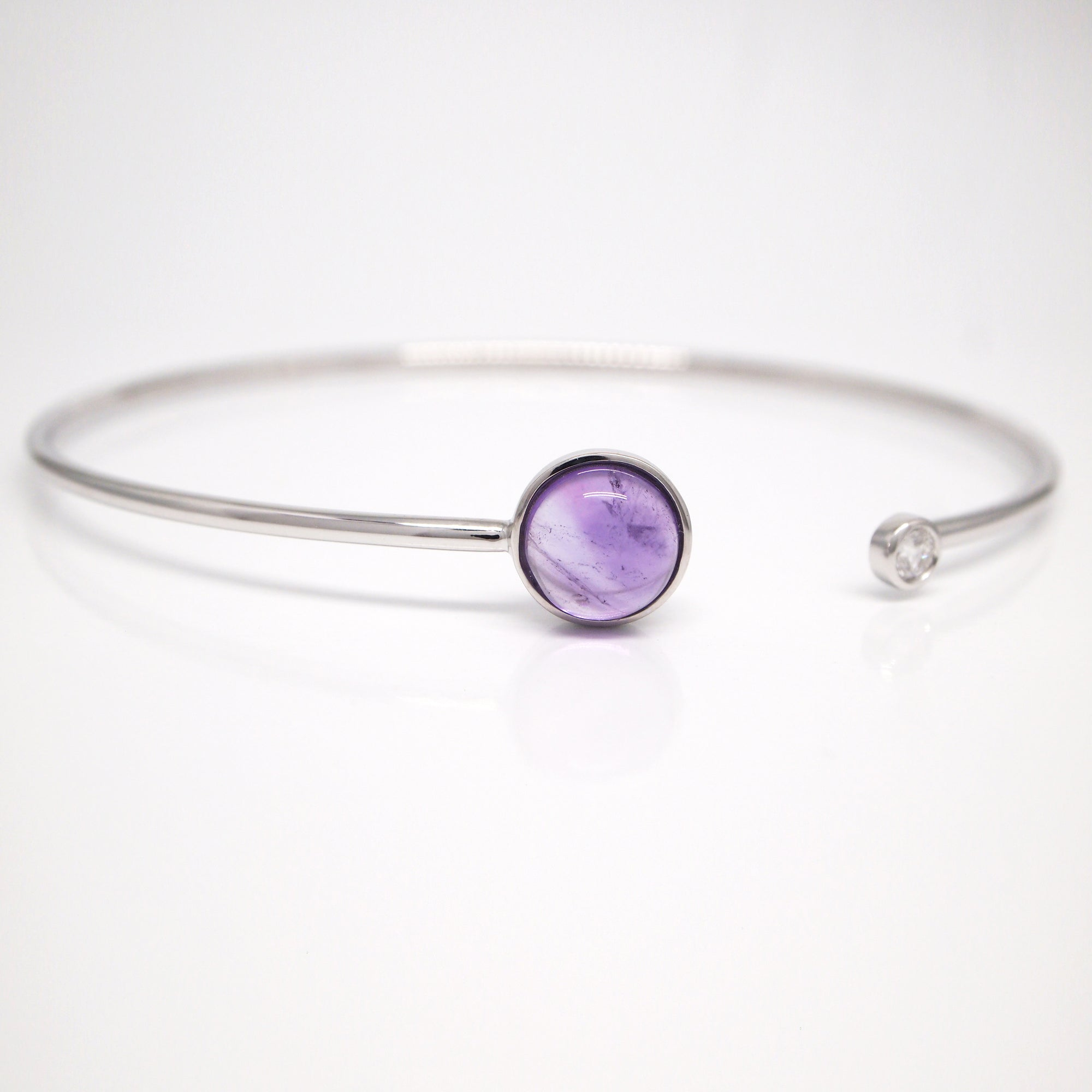 14K white gold bangle bracelet featuring an 8mm cabochon-cut amethyst and a bezel-set brilliant-cut diamond