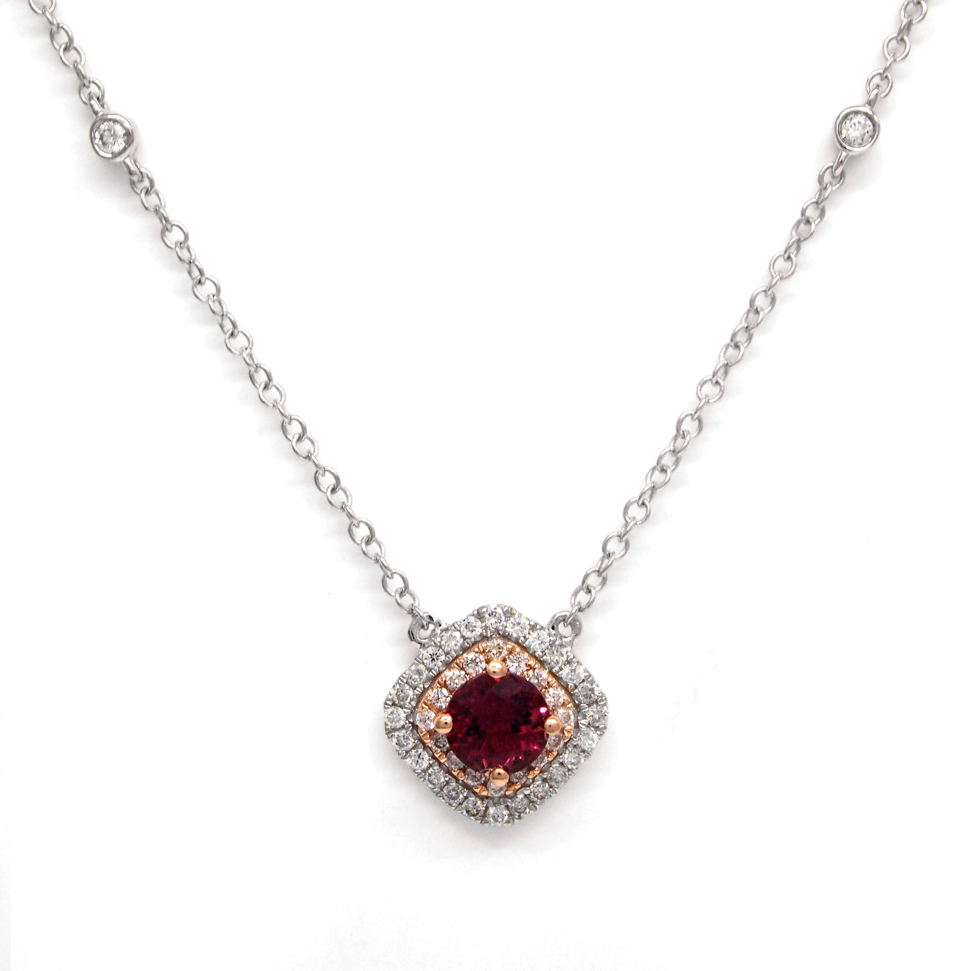 14K two-tone white and rose gold necklace featuring one 0.47 carat round pink tourmaline, and double halo with round brilliant diamonds weighing a total of 0.23 carats.