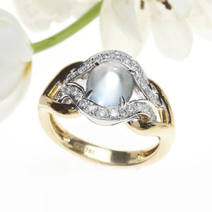 Angled View of White and Yellow Gold Two Tone Cabochon Cut Moonstone Ring with Round Brilliant Diamonds