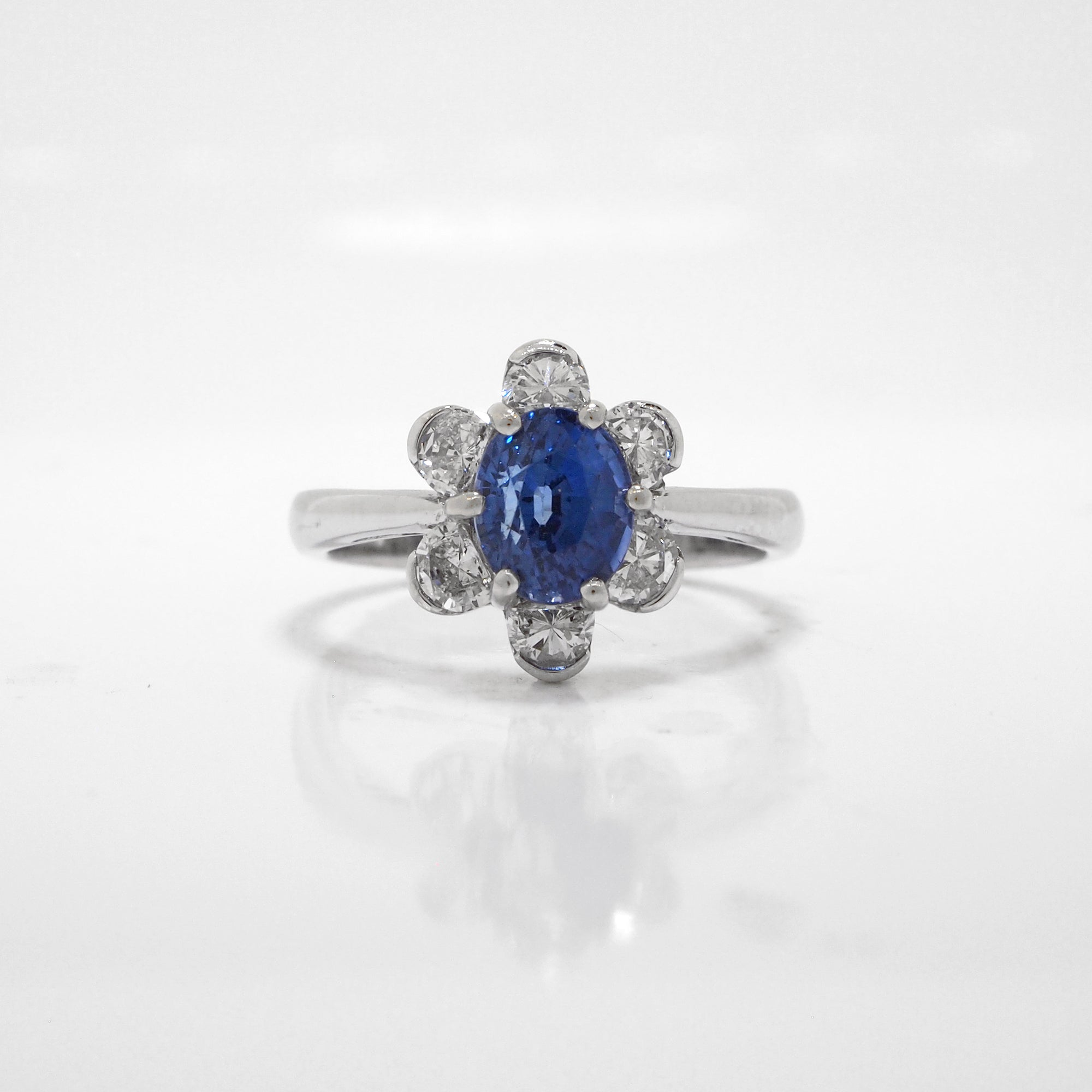 18K white gold sapphire and diamond ring featuring one 1.70 carat oval blue sapphire, and a 6 diamond halo with diamonds weighing a total of 0.56 carats.